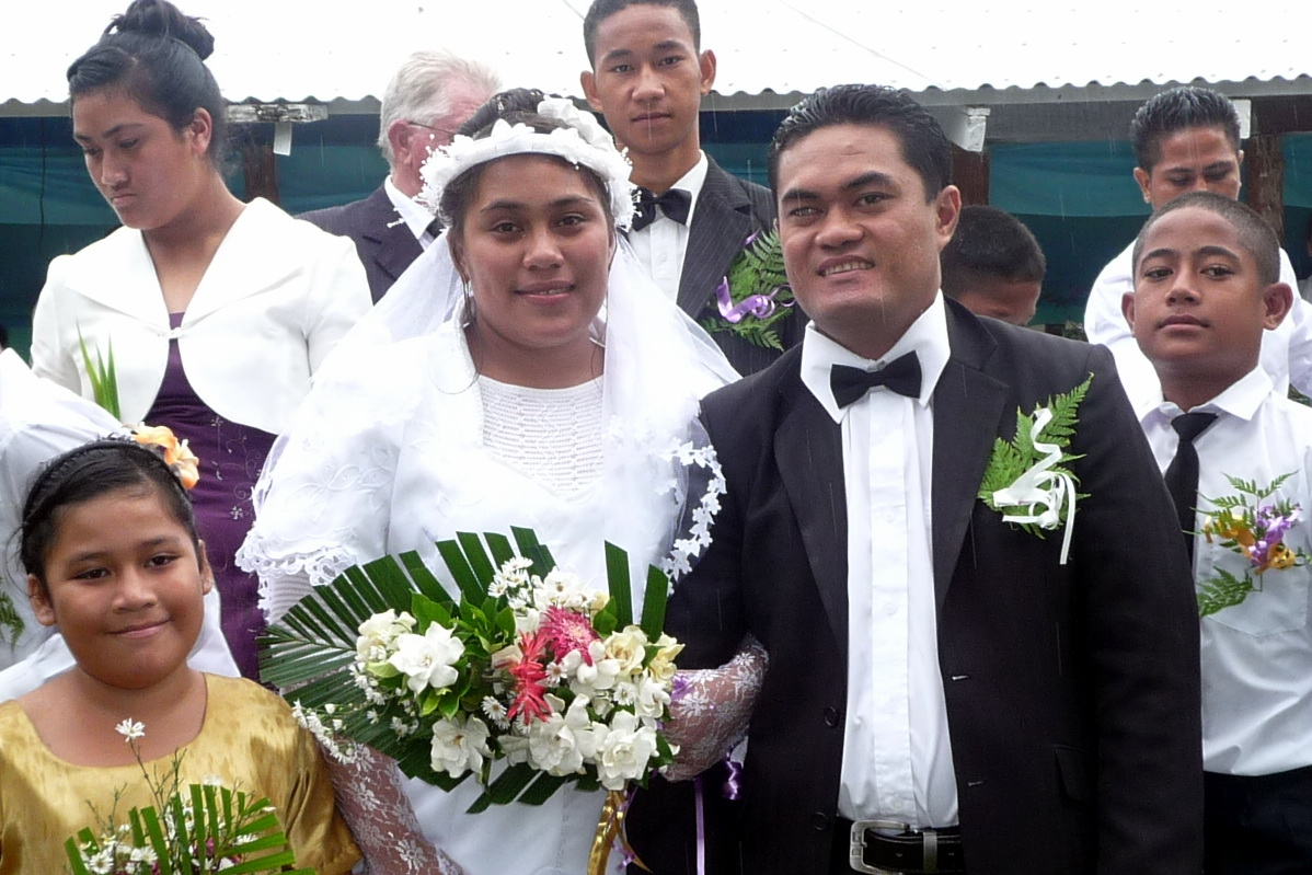 Despite the rain, the wedding party paused for photos outside the Church Fale, F
